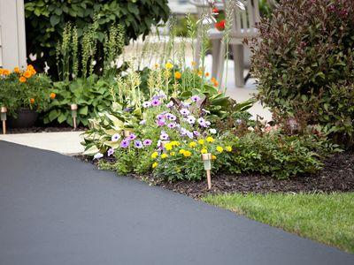 Asphalt driveway with green grass, flower beds, and a sidewalk.
