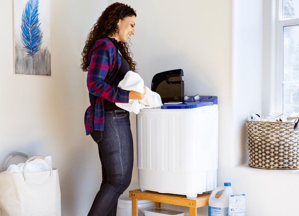 Woman using a portable washing machine