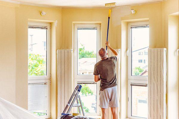 Man painting room ceiling