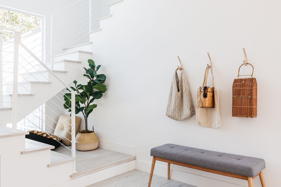 White entryway with staircase near window with gray bench and hooks with bags hanging