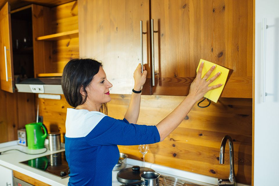 Side View Of Woman Cleaning Cabinet In Kitchen At Home