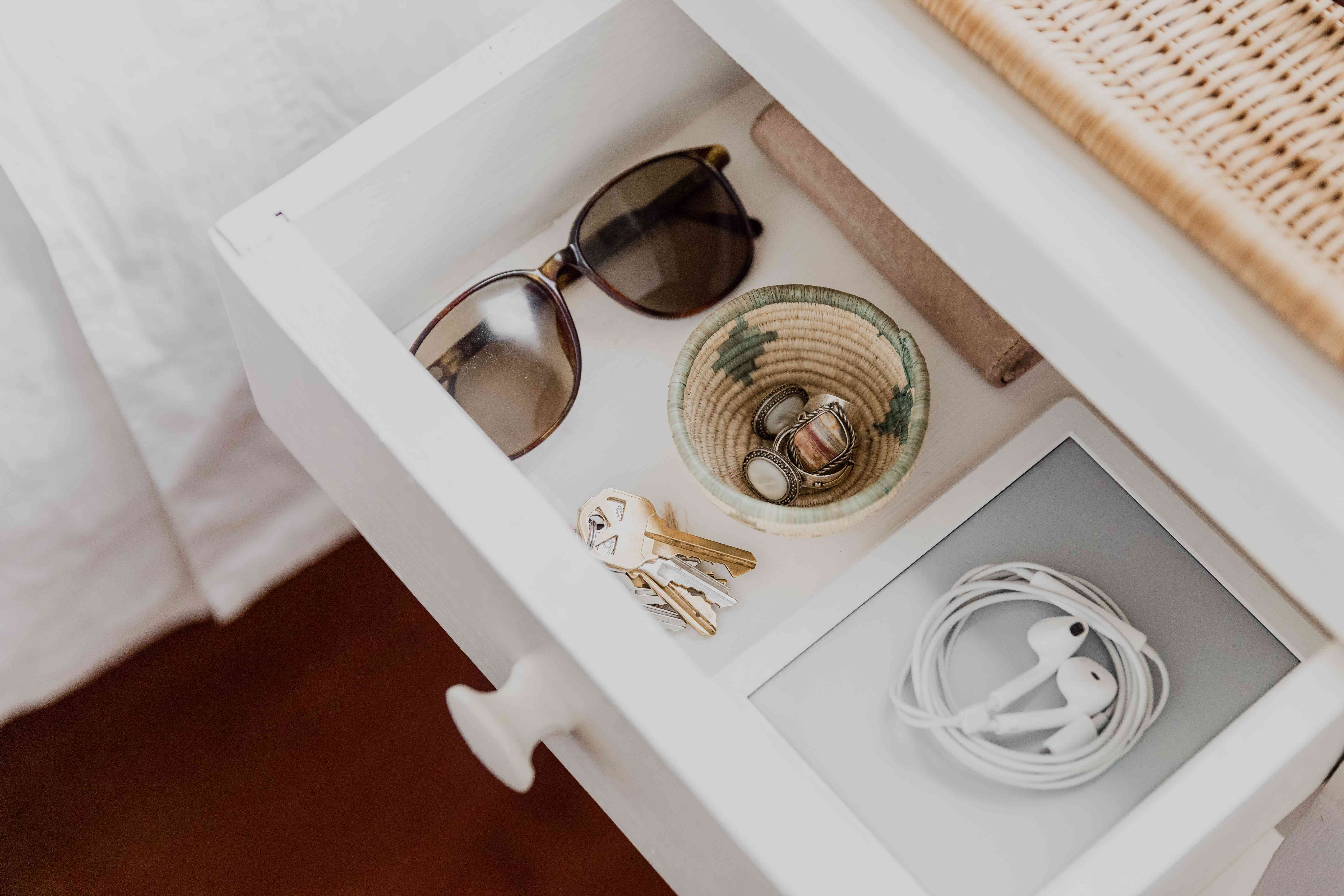 Sunglasses, keys, earphones and jewelry organized inside nightstand drawer