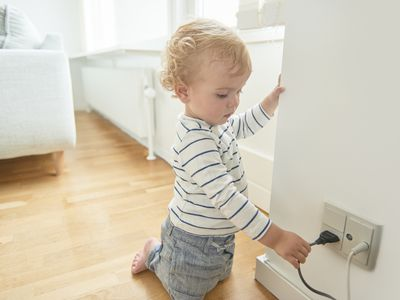 Baby boy touching electrical plug in the wall.