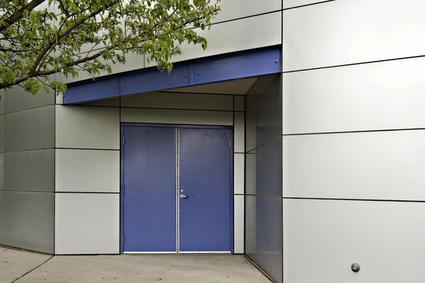 Two blue steel doors on a commercial building.