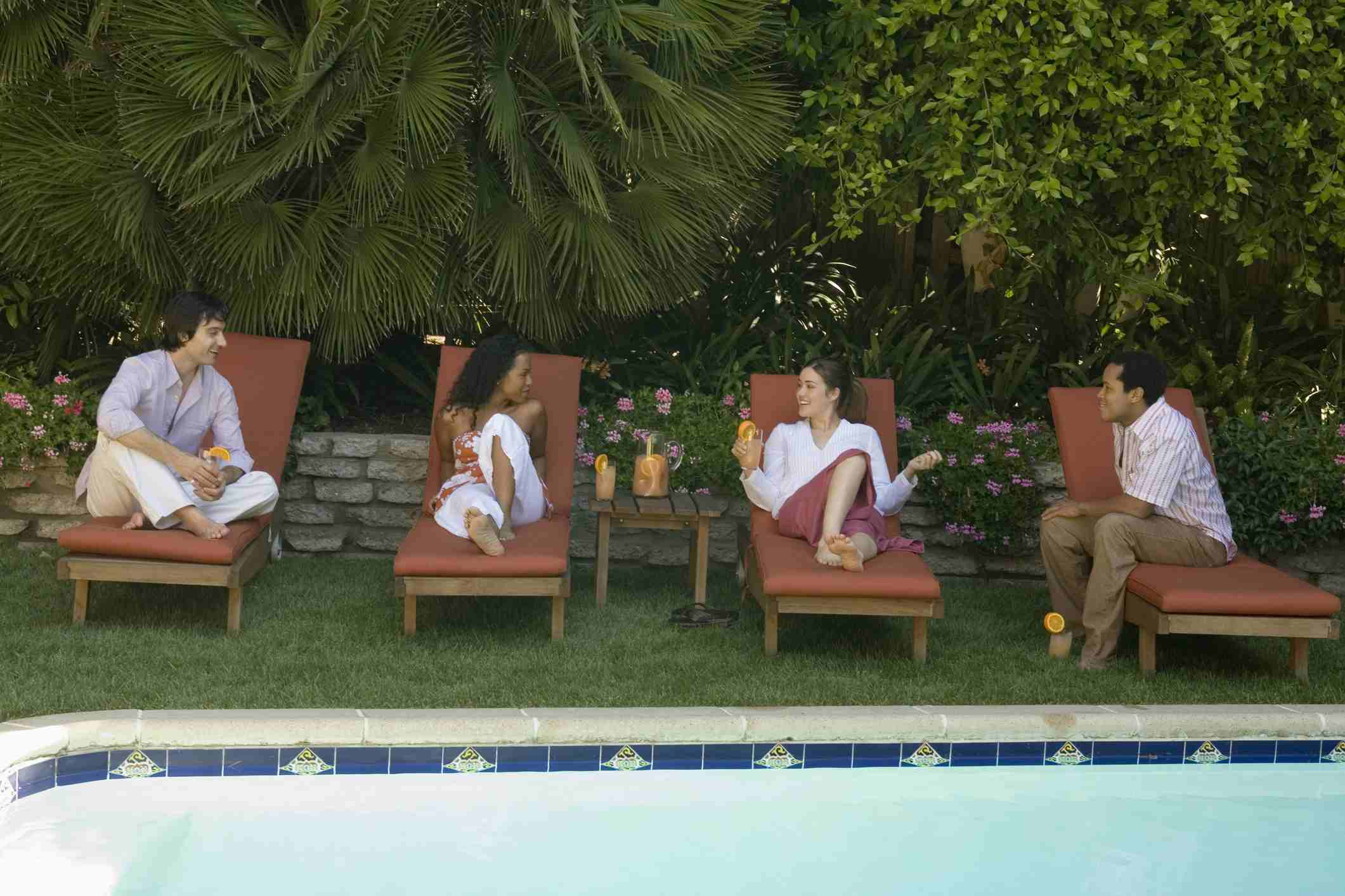 Four people on lounge chairs near swimming pool.
