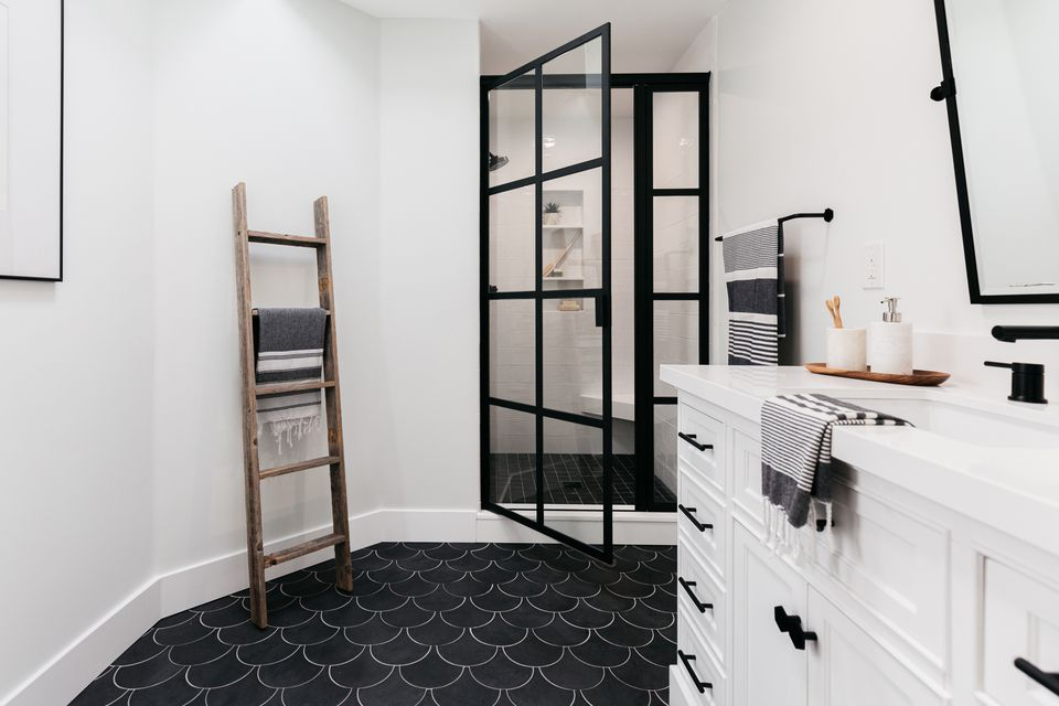 Black and white bathroom with white cabinets and black rimmed shower door