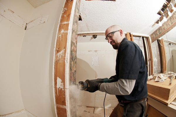 Worker undergoing master bathroom remodeling project and using a saw to cut the walls.