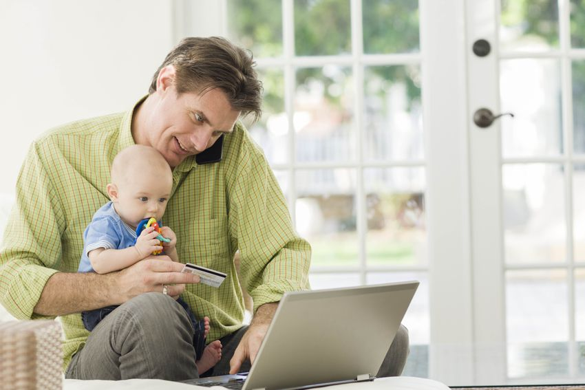 Father Shopping Online with Baby in Lap