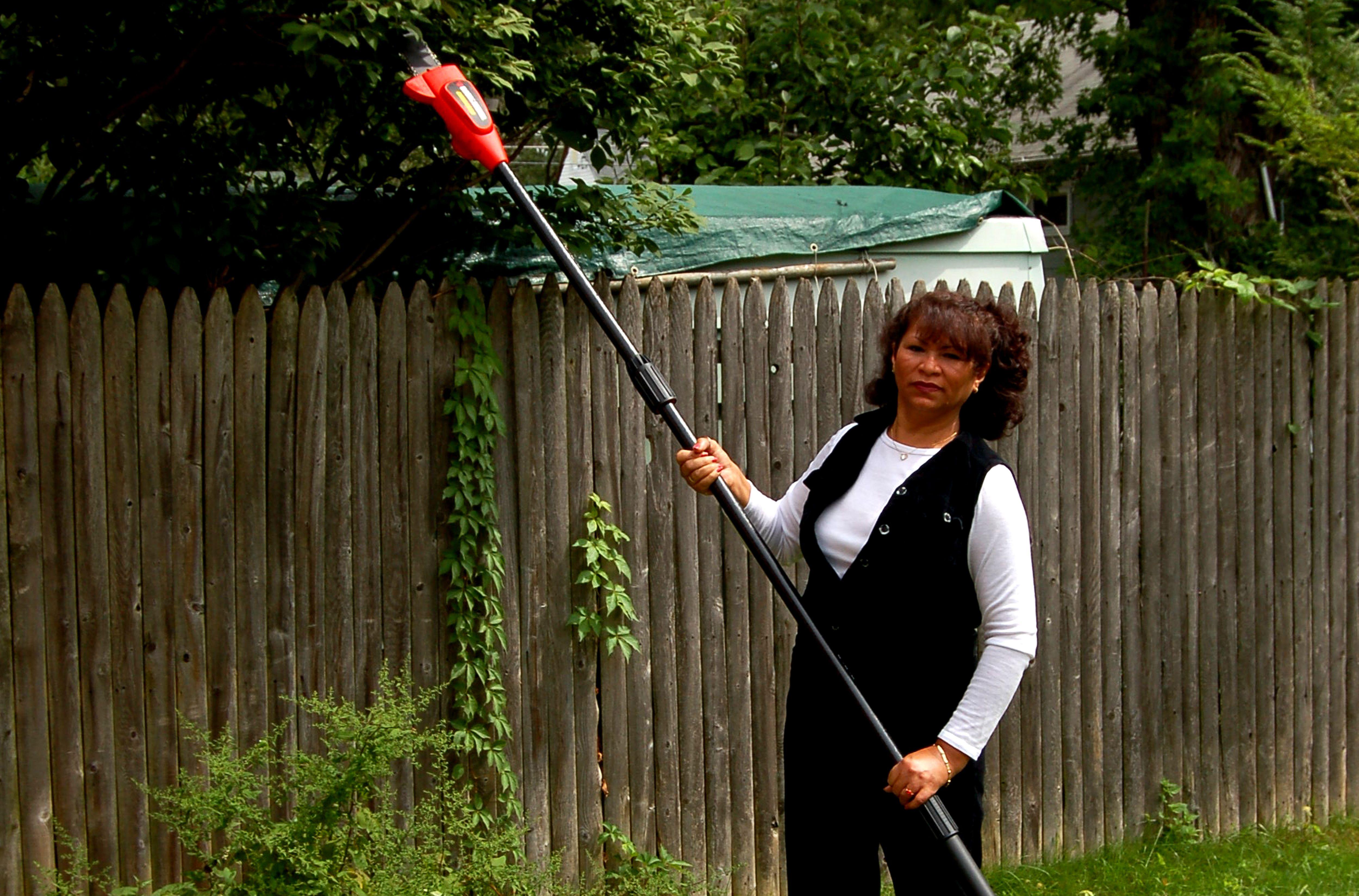 Woman holding Black & Decker pole chainsaw
