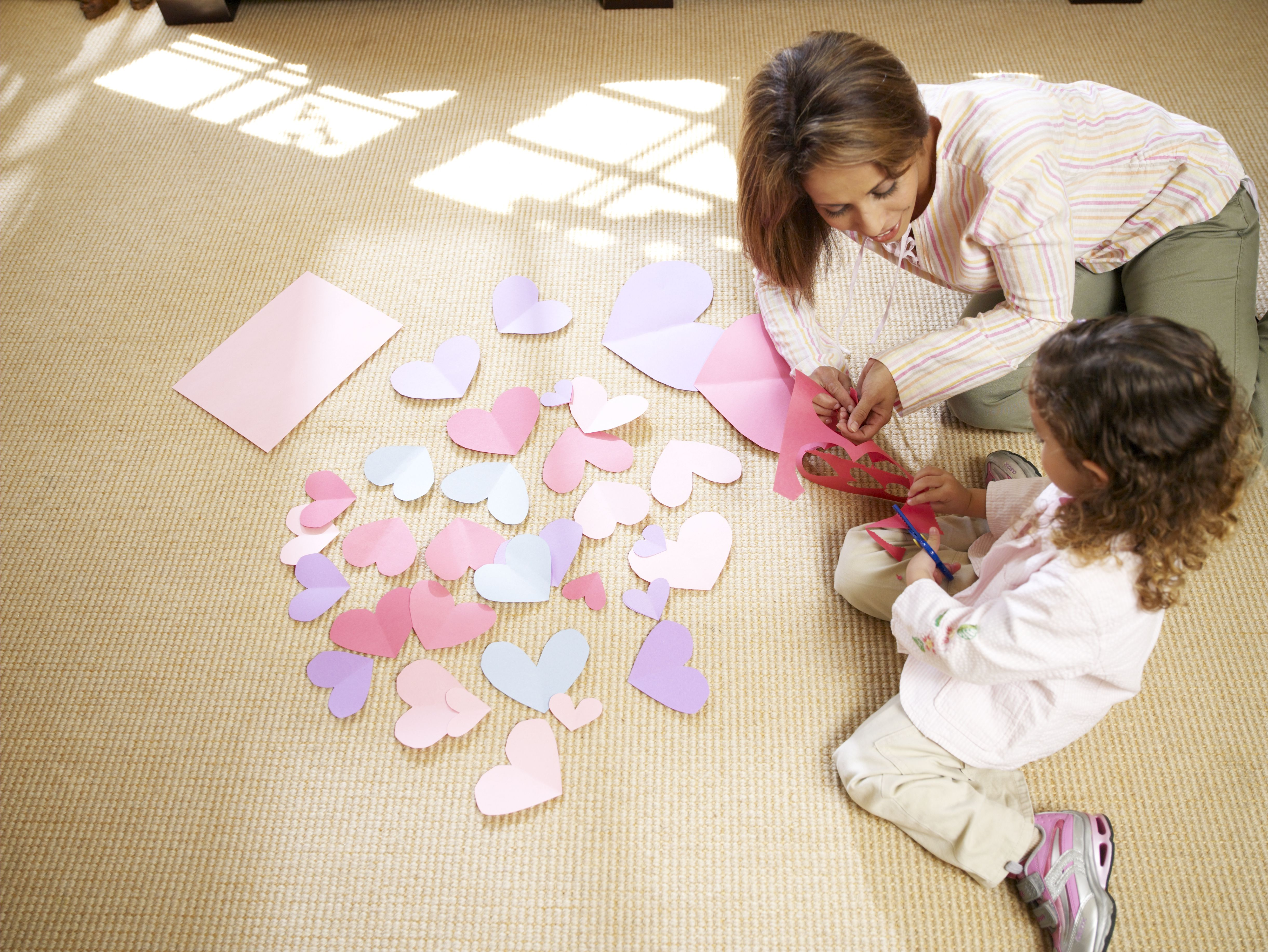 Mother assisting daughter (3-4) cutting off heart shape of paper