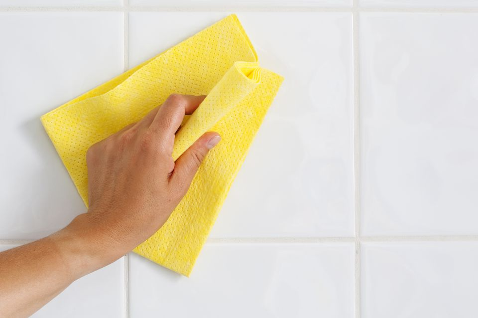 person cleaning shower tile with washcloth