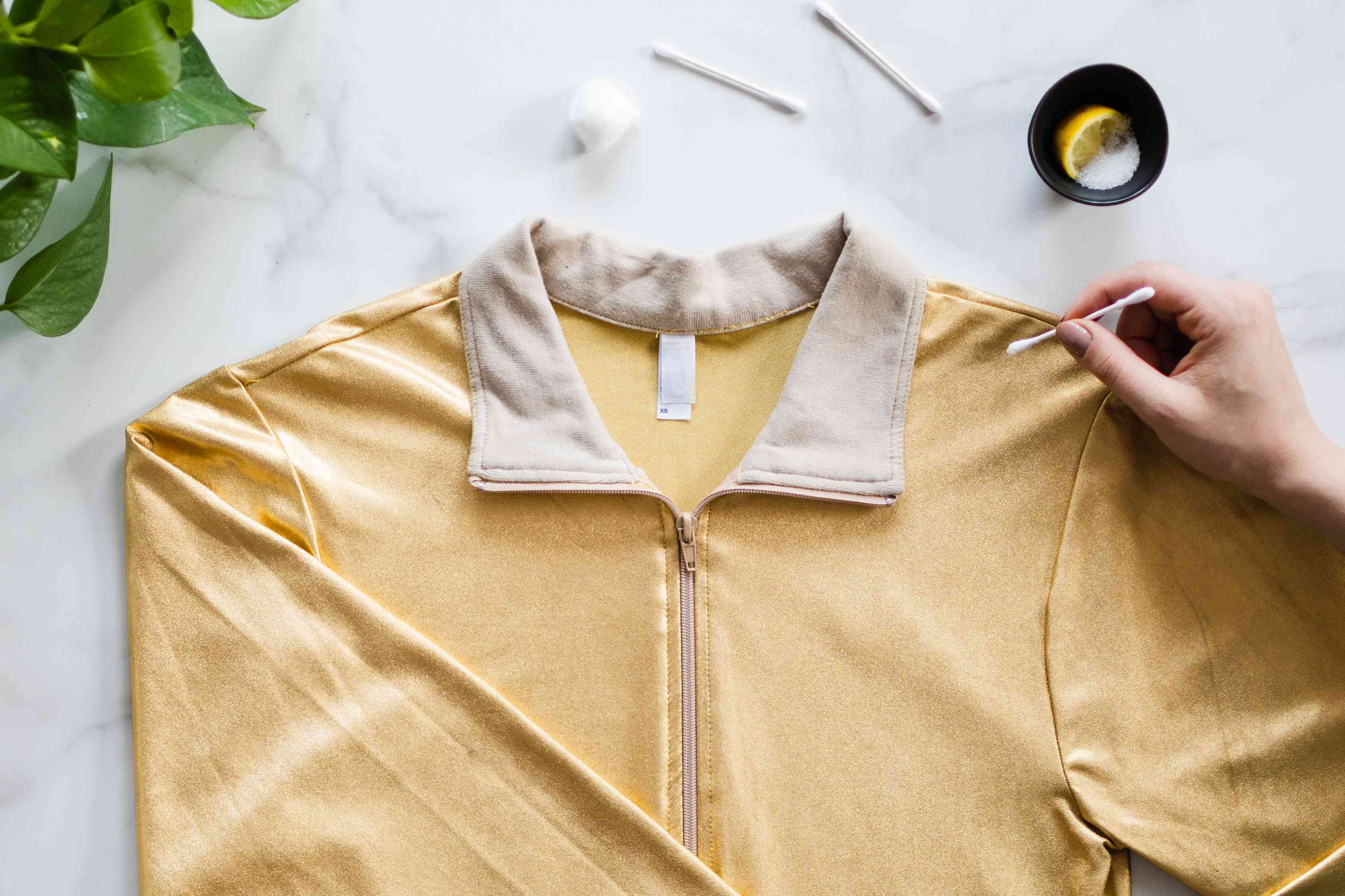 Cotton swab with lemon juice and salt applied to yarn tarnish on yellow metallic jacket