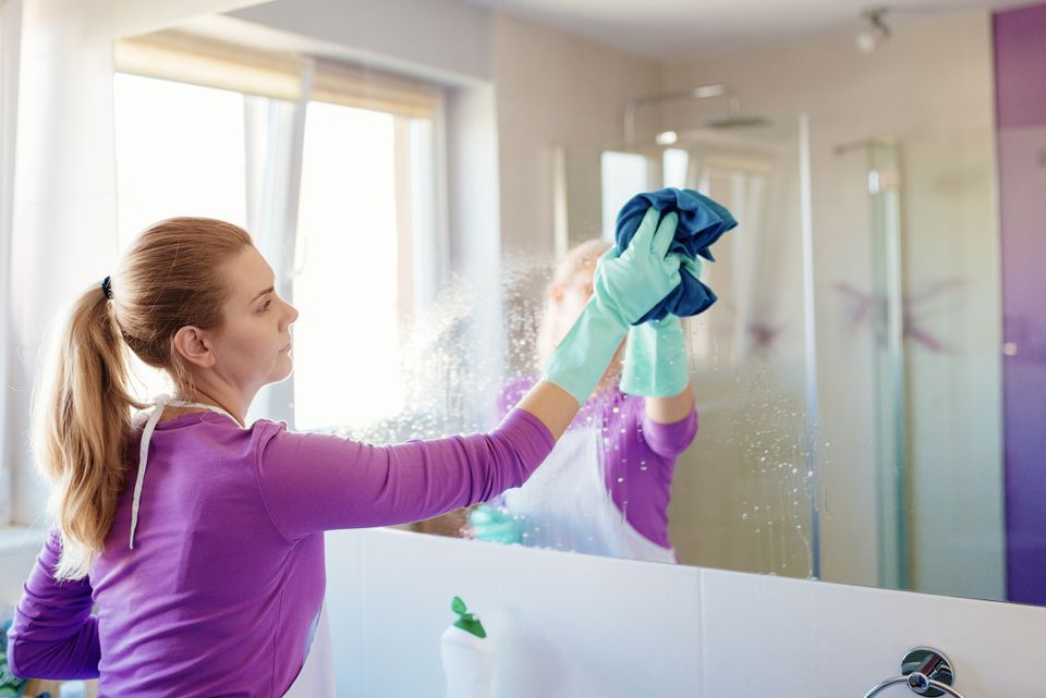 Woman cleaning bathroom mirror