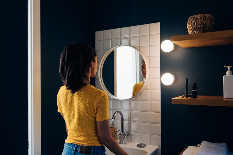 Young woman in front of wall mirror in bathroom