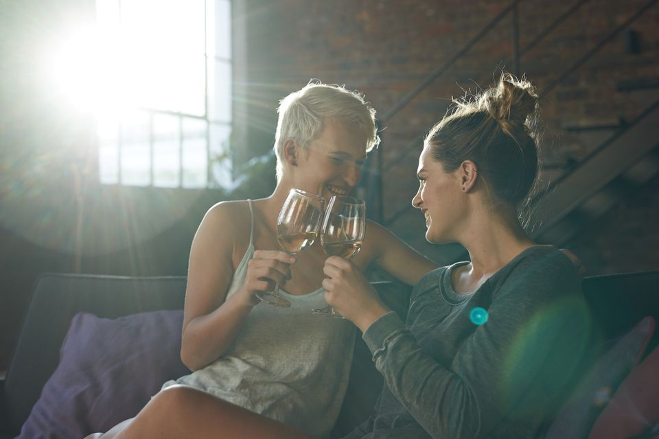 Lesbian couple celebrating with wine