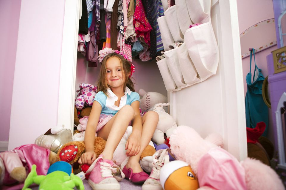 Little girl sitting in an armoire with toys and shoes surrounding her