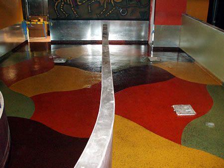 revestimiento de piso de concreto pintado con epoxi con naranja, amarillo, marrón y verde .