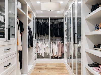 Walk-in closet with recessed and hanging lighting and white cabinets and shelving