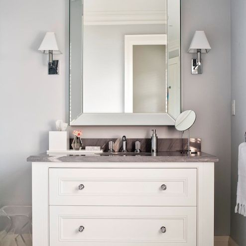 Grey and white bathroom with white vanity and silver mirror.
