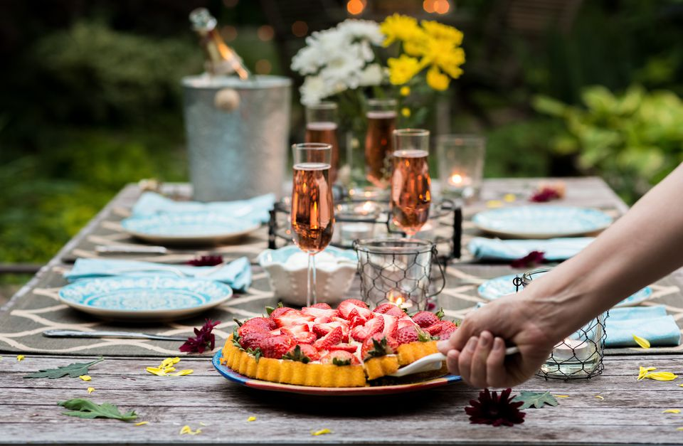 Table set for outdoor dining with dessert course and pink champagne by candlelight