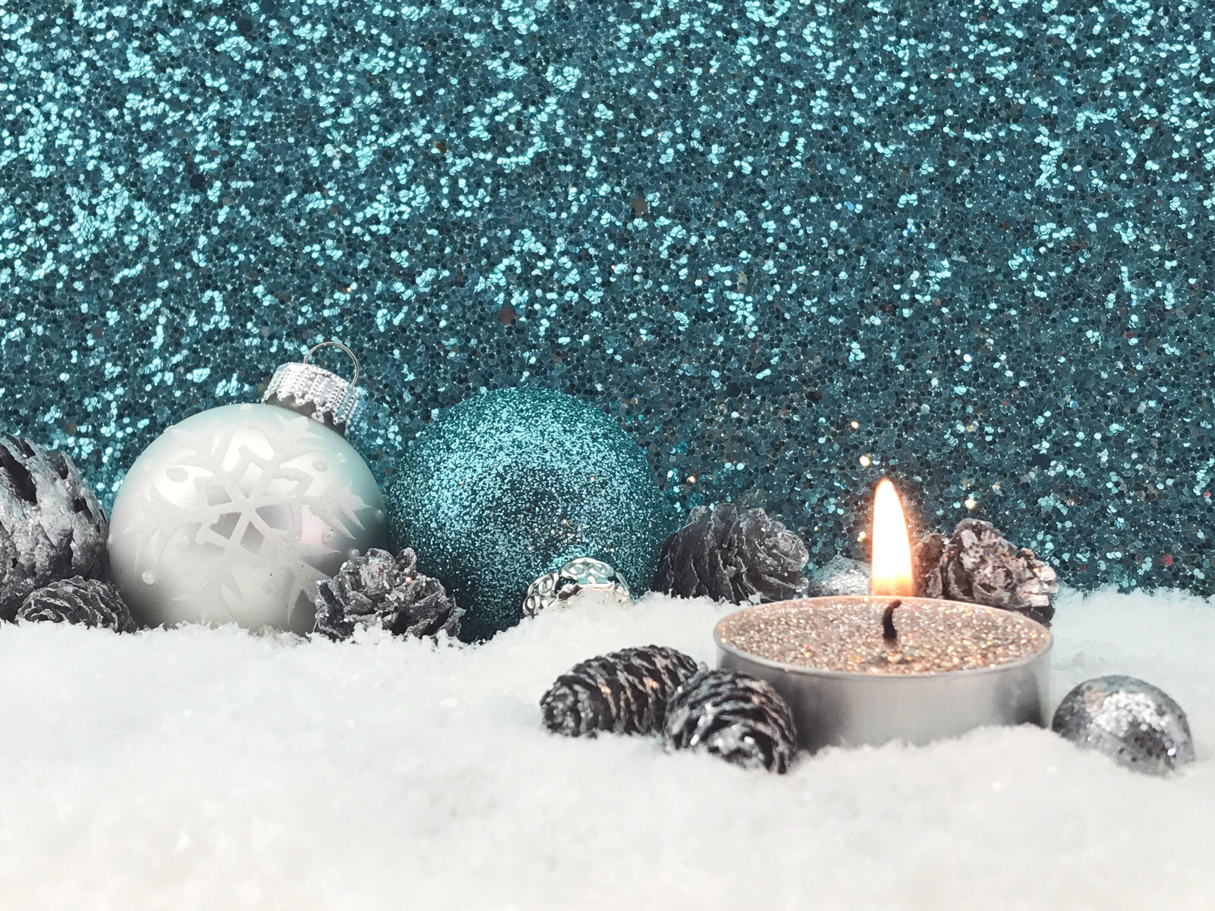 Lit Candle With Christmas Decoration On Fake Snow Against Glittering Wall