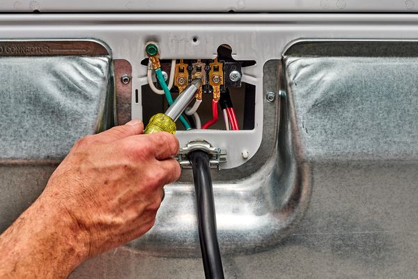Electrical cord installed in back of dryer machine with screwdriver