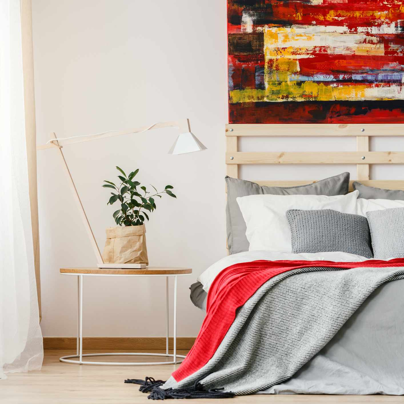 Grey and red blanket on bed next to table with lamp and plant in bedroom interior with painting.