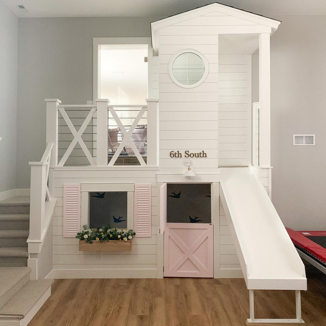 A kid's playhouse with a slide, a window box filled with faux flowers and a pink door.