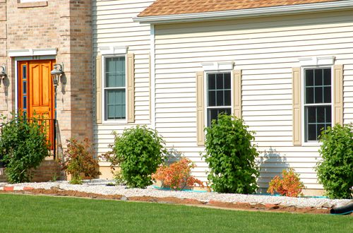 The foundation shrubbery is nicely set off by a white stone mulch.