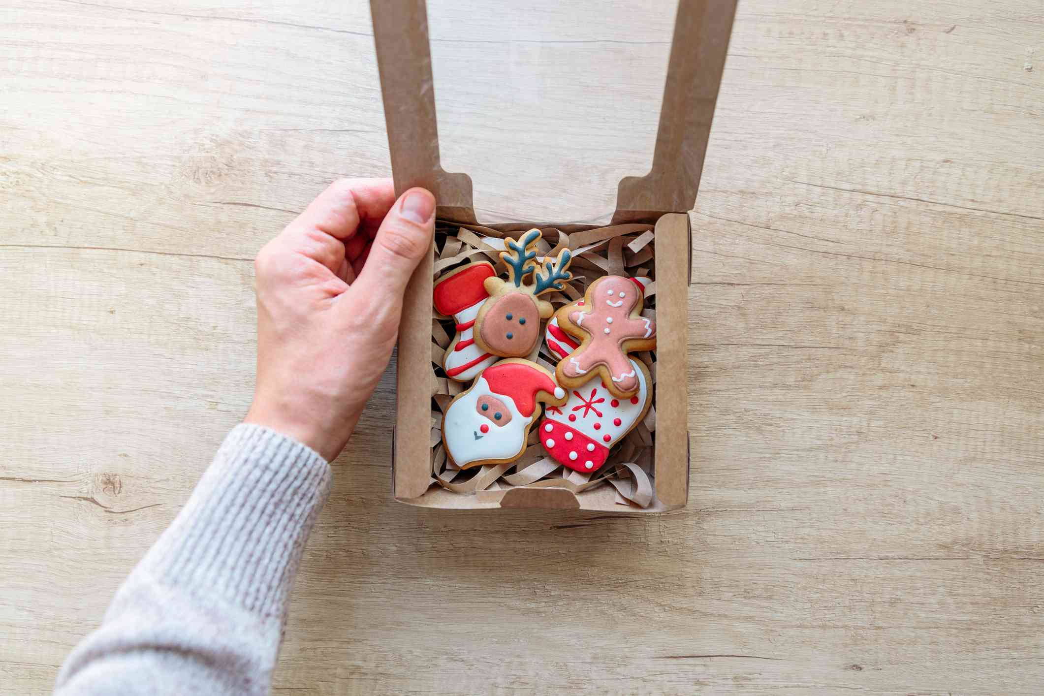 Opening Christmas present with Christmas cookies, personal perspective view