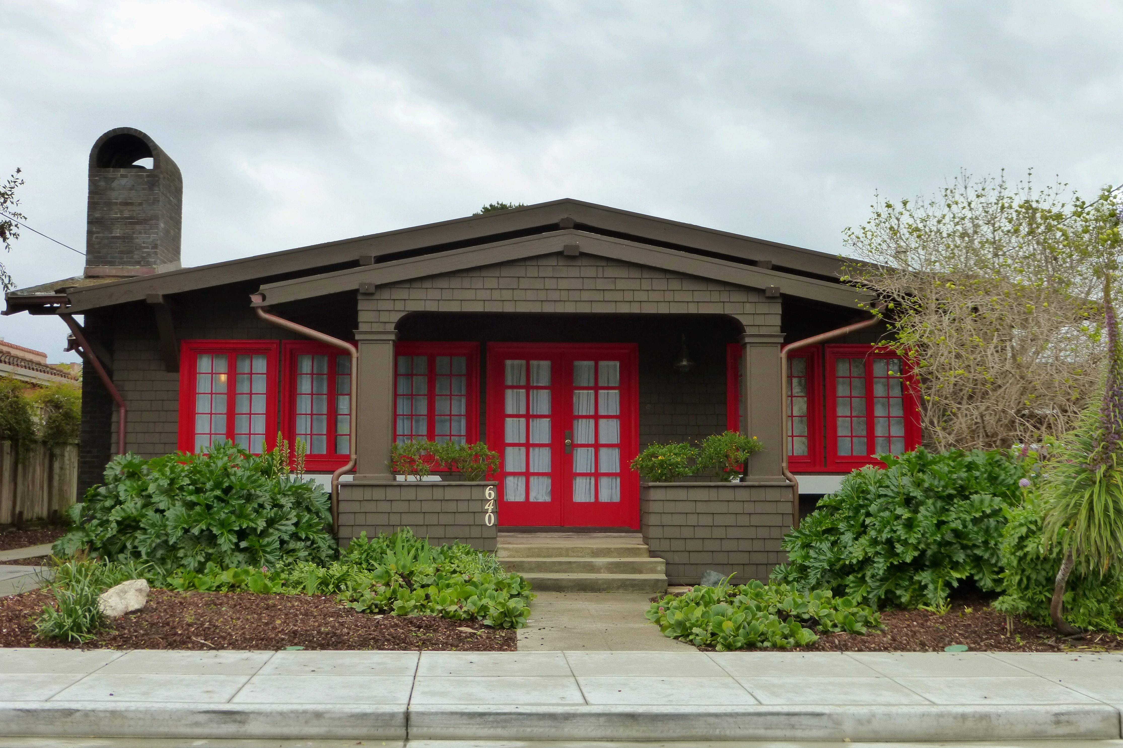 Front view of brown-shingled bungalow with red doors and windows