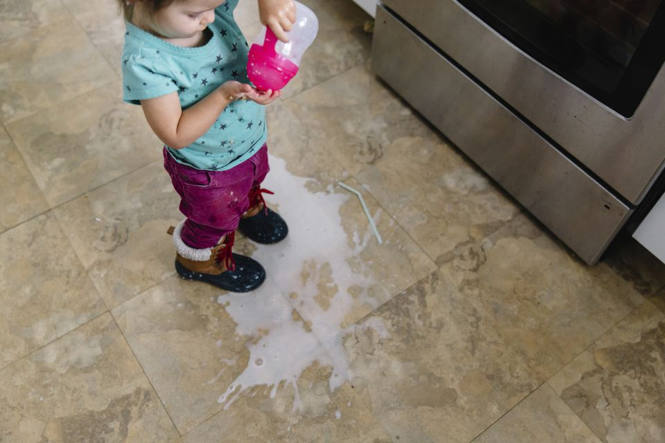 Young girl with spilled milk in kitchen