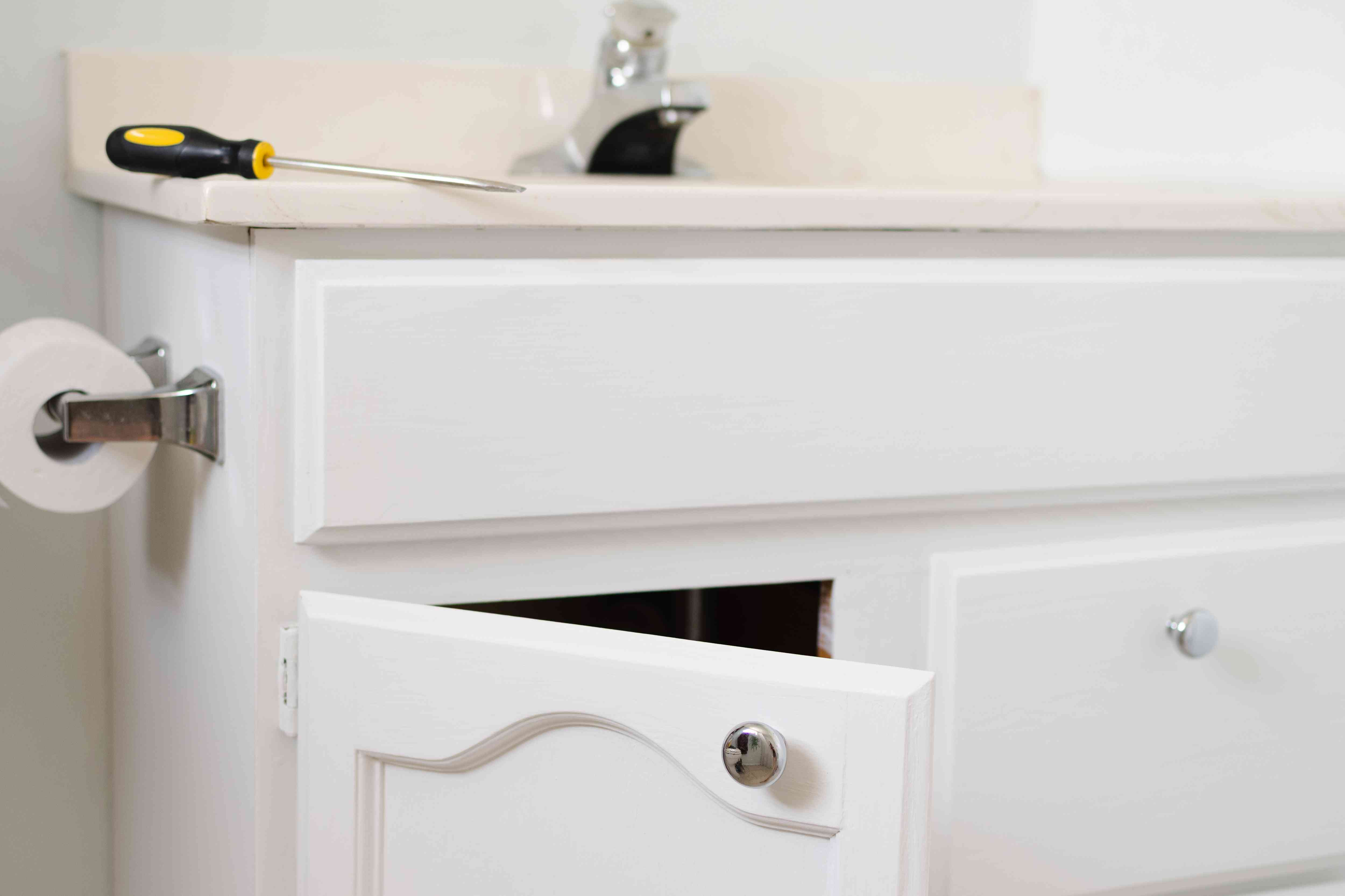 White bathroom cabinets reattached back in place in bathroom with screwdriver