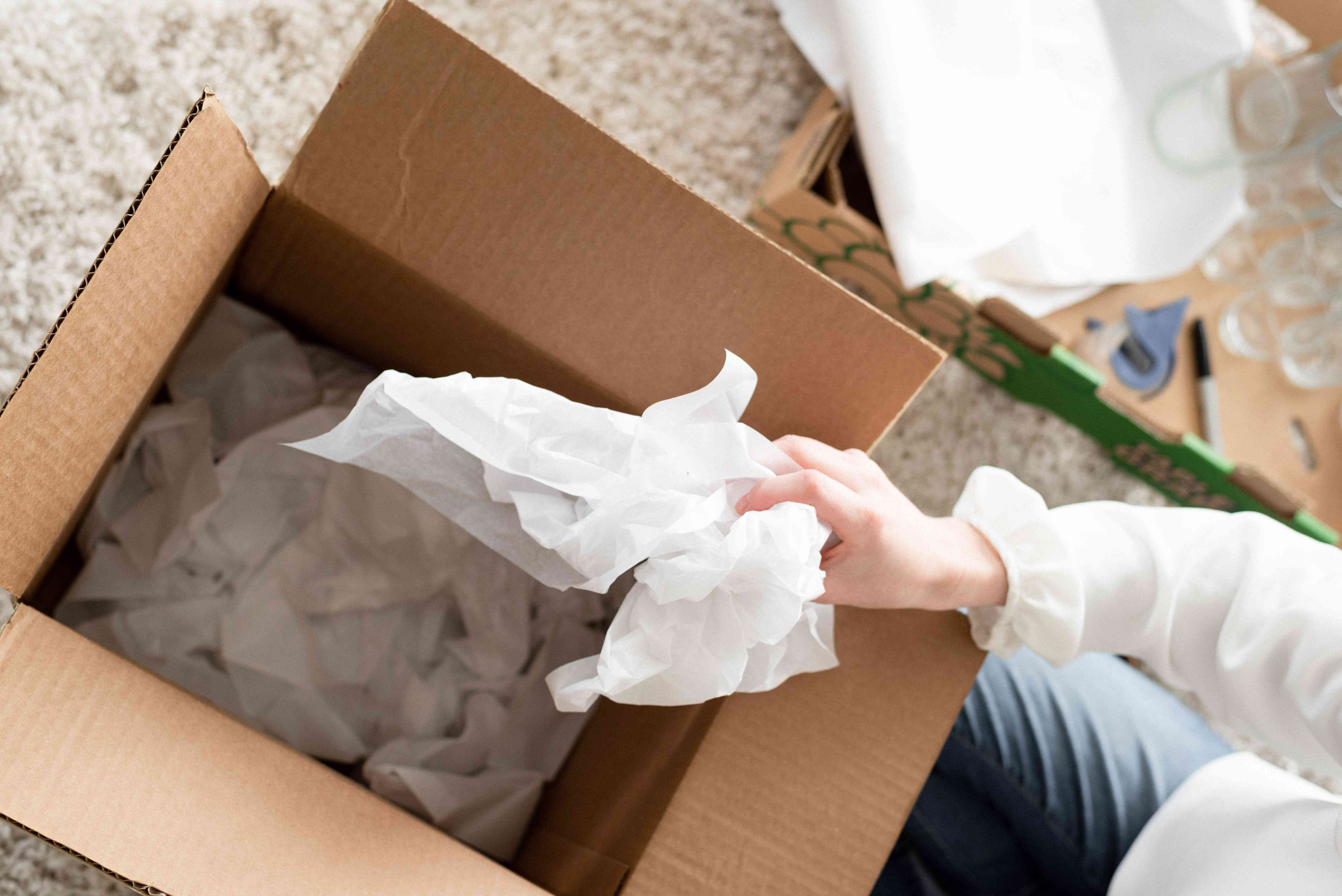 person crumpling packing paper