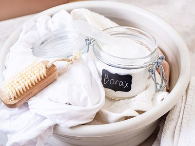 Glass container of borax with soft bristled brush and fabric in bucket