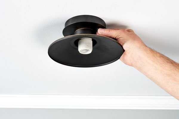 Black light fixture getting light bulb replaced by hand