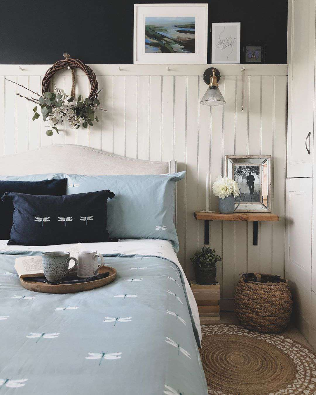 Bedroom with blue walls and white paneling