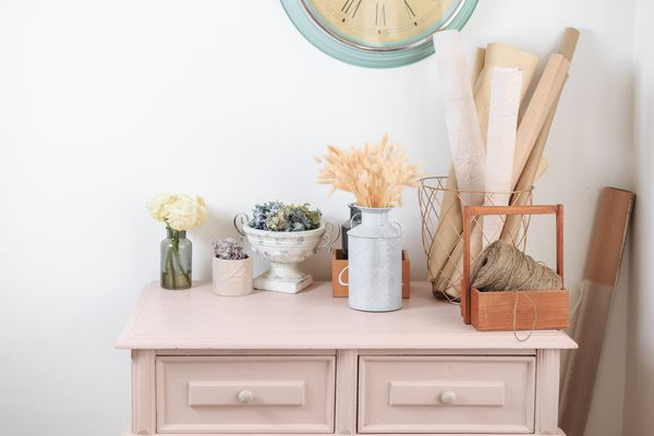 pink painted dresser in a white room