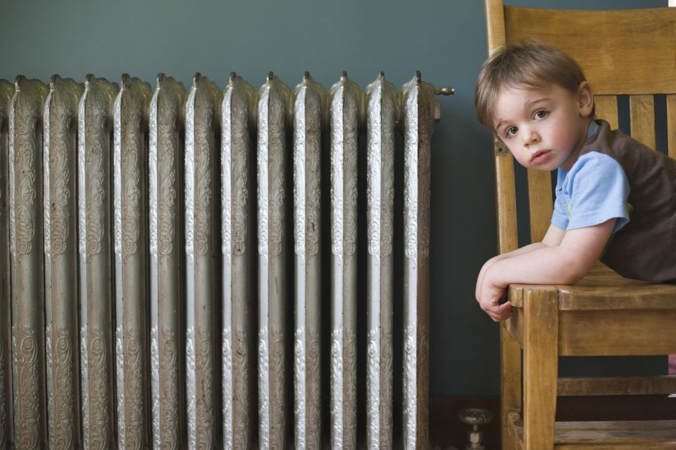 A Child on a Chair Next to a Radiator