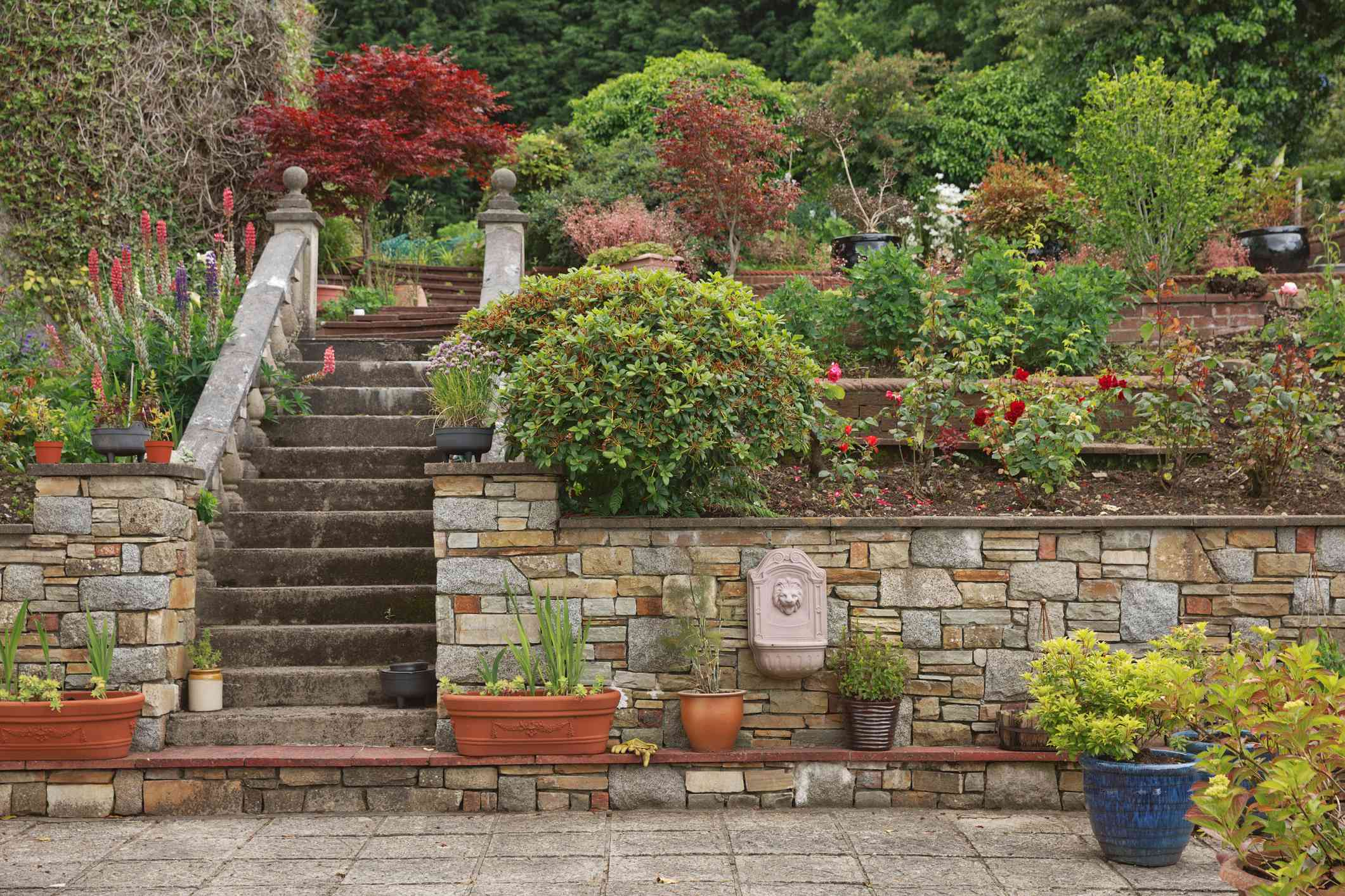 Natural stone steps and retaining wall, planter and garden border framing home entrance