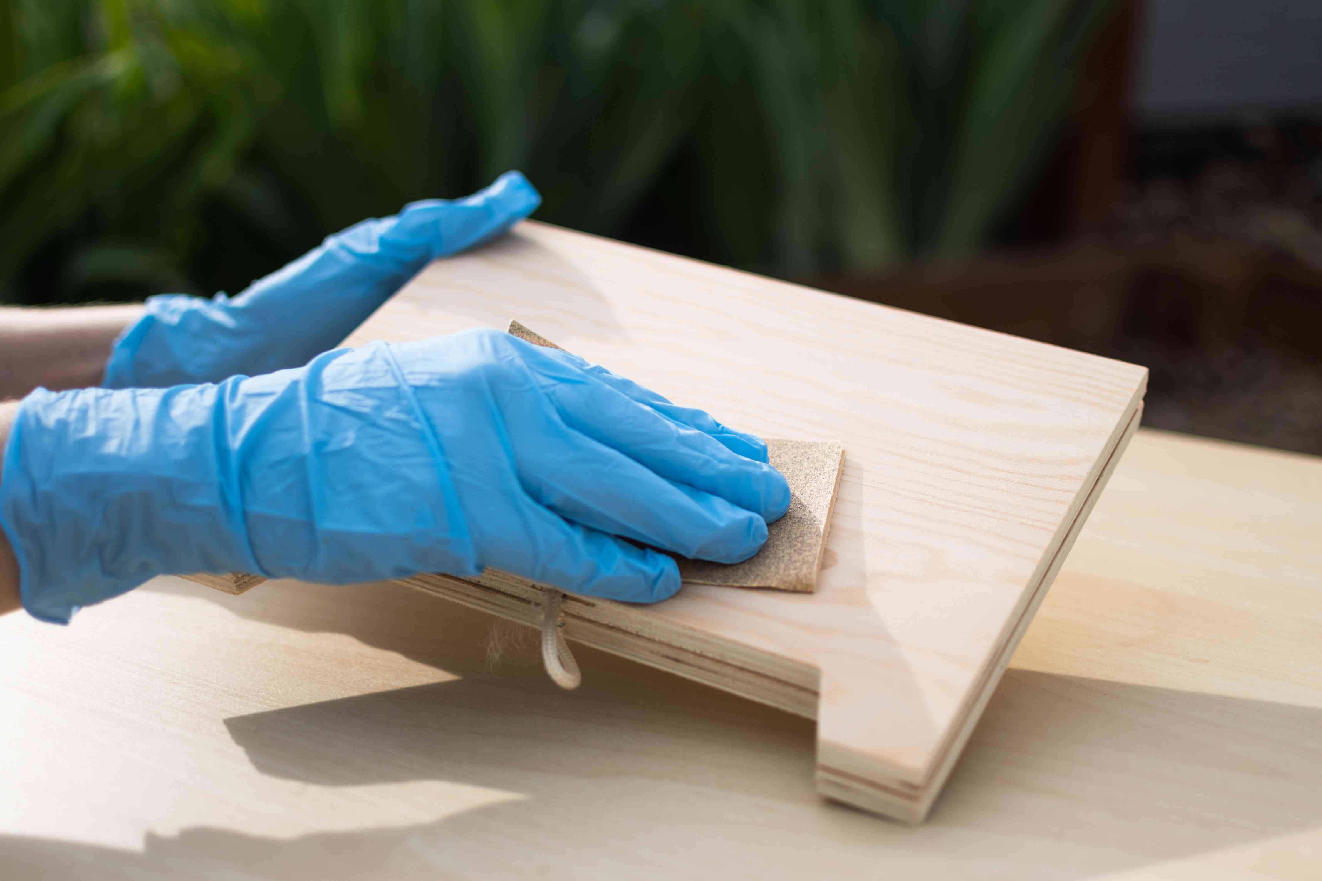 Wooden sign sanded down with fine-grit sandpaper while wearing blue gloves