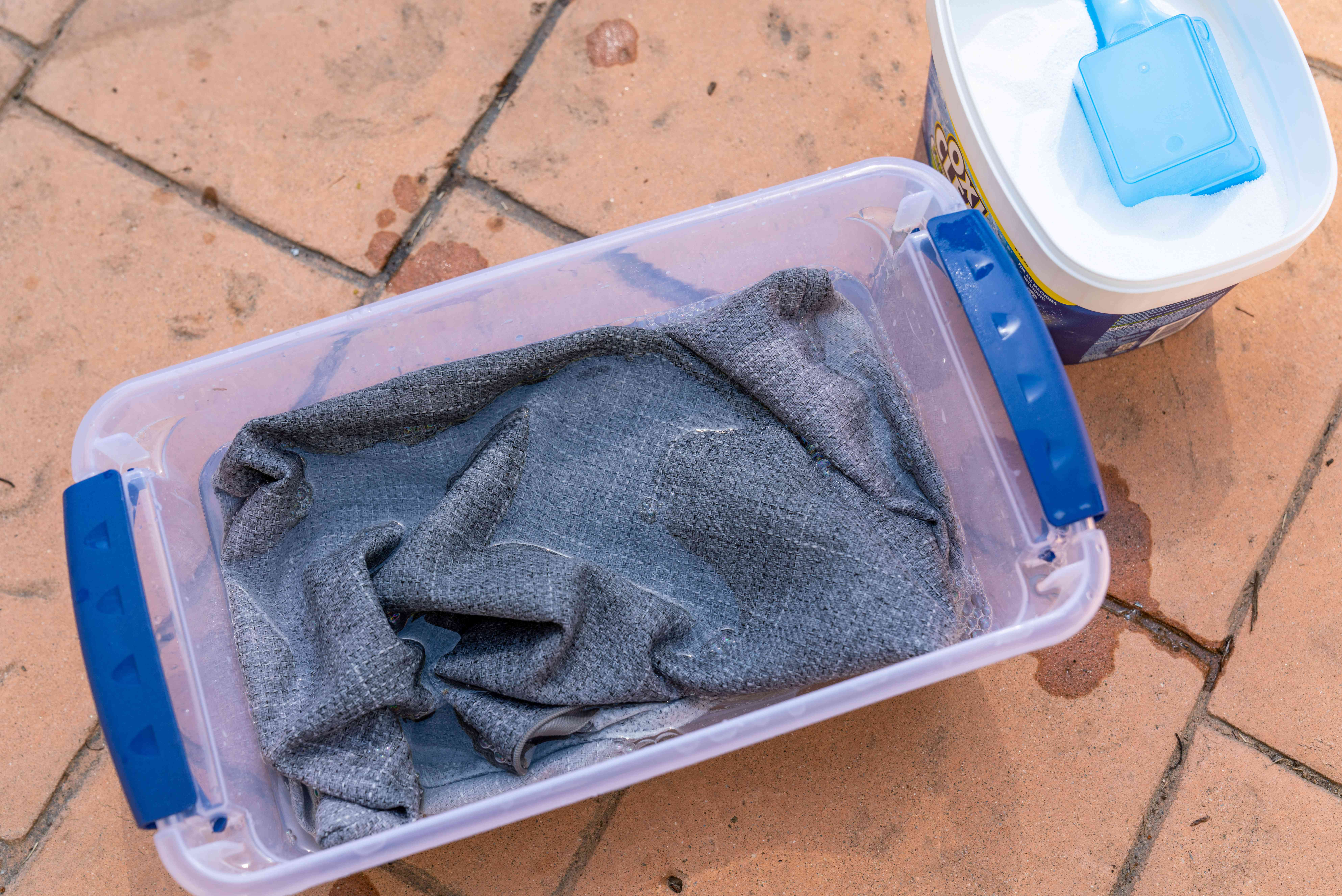 Outdoor furniture fabric soaked in plastic container with hot water and oxygen-based bleach