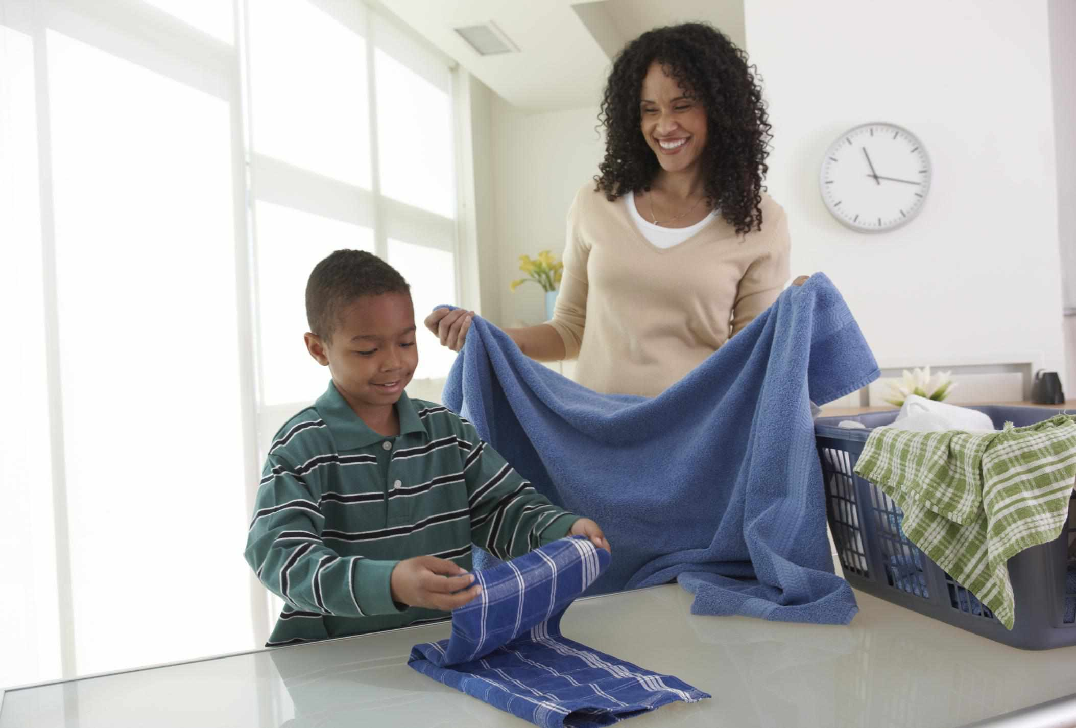 Mother and son folding laundry together