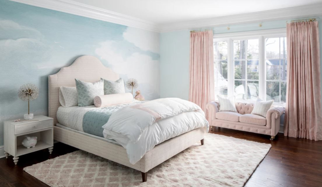Teen bedroom with accent wall painted like clouds and large tufted bed.