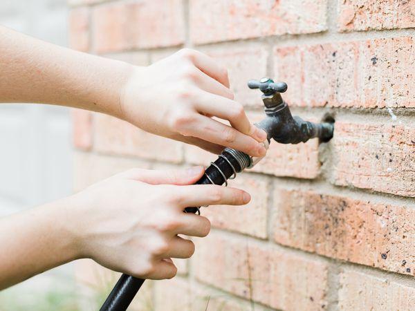 person checking an outdoor spigot