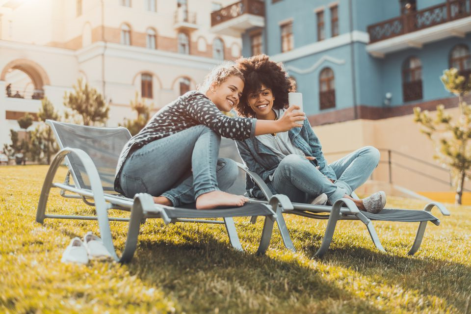Young female couple sitting on outdoor recliners taking a selfie