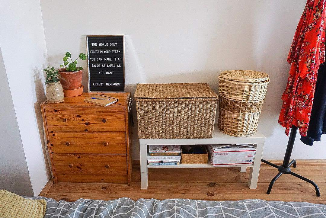 A bedroom wall with a dresser and various accessories and clothes