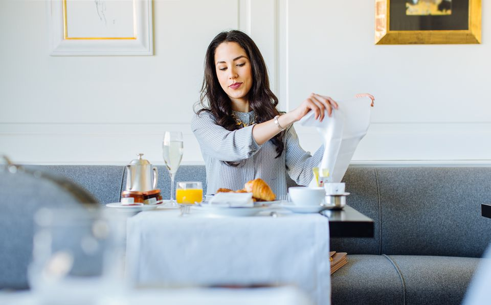 Young woman preparing napkin whilst having champagne breakfast at boutique hotel in Italy