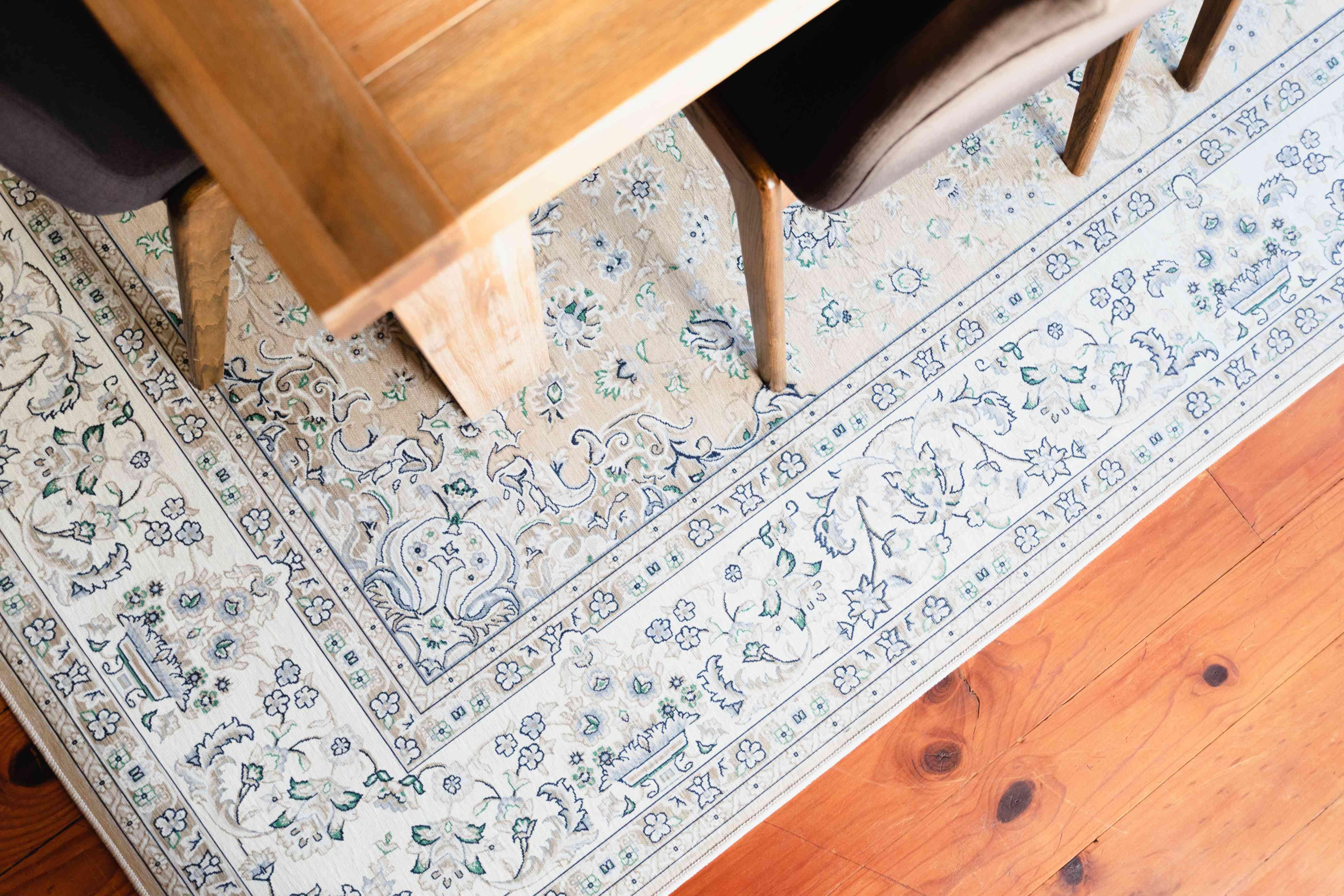 Light colored patterned rug under corner of dining room table