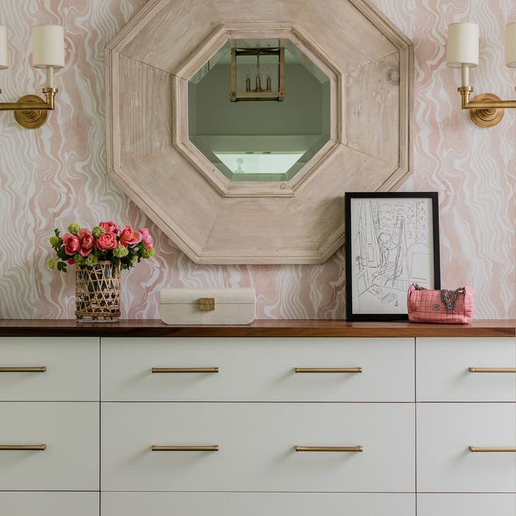 pink swirls wallpaper sets the tone in this bedroom with white dresser, sconces, and fresh flowers